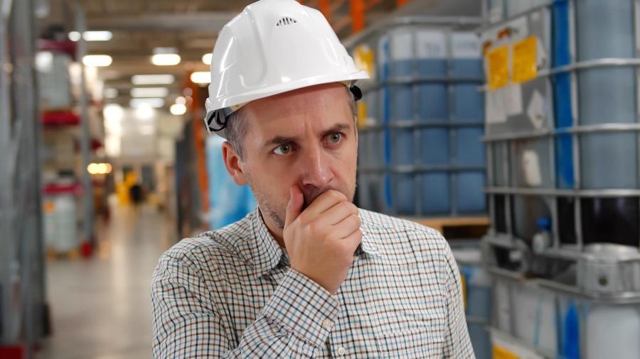Mann hustet in Fabrikgebäude - Arbeitsschutz in der Chemie