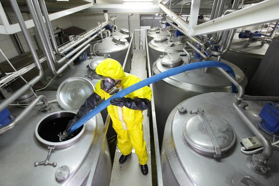 Jemand befüllt einen großen Metallcontainer per Schlauch - Arbeitsschutz in der Chemie